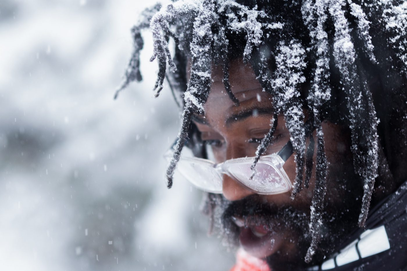 Close up portrait of a black man with snow in his hair.