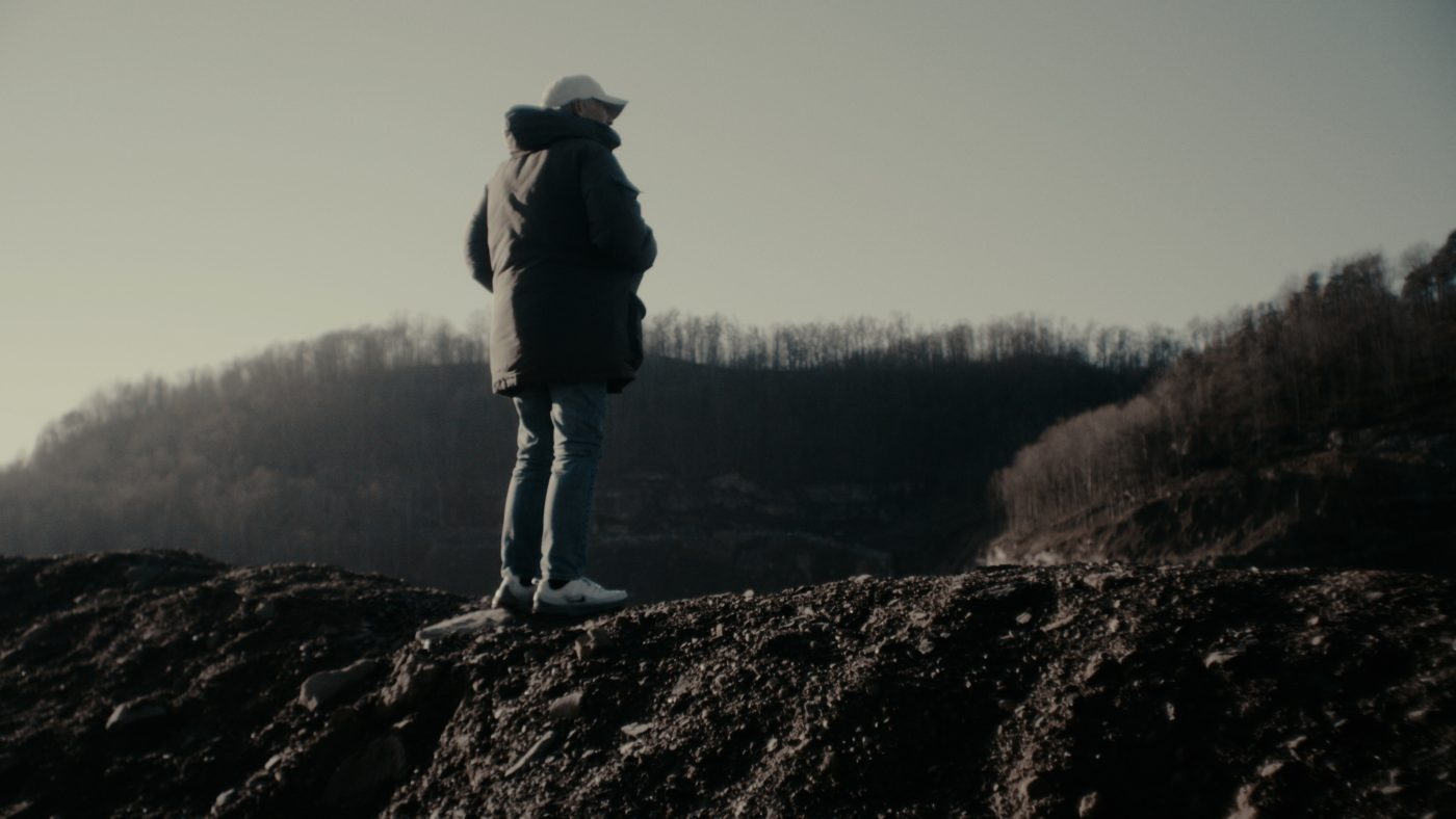 A man in a coat and jeans stands on a rocky hill facing away from the camera, with brown trees in the background.