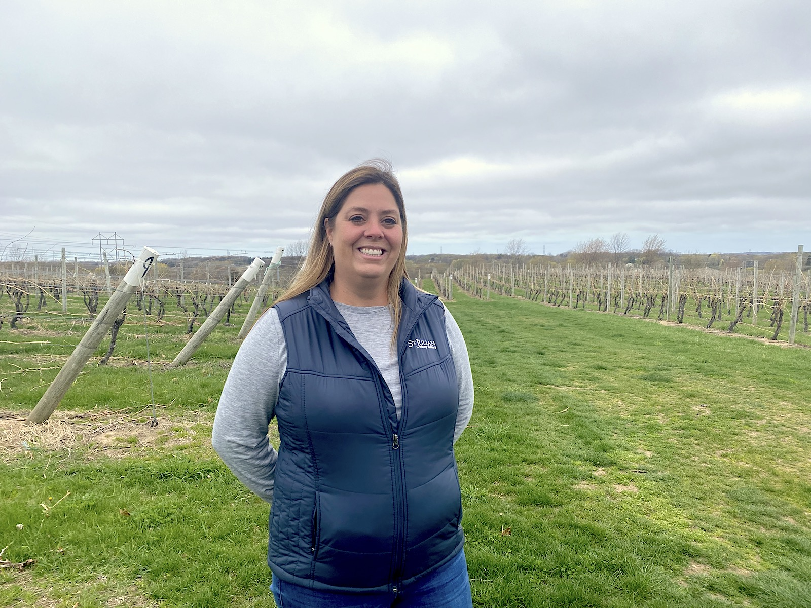 A photo of a woman in a black puffer vest and a long blue-gray shirt. She has blonde hair and is smiling. In the background are green fields.