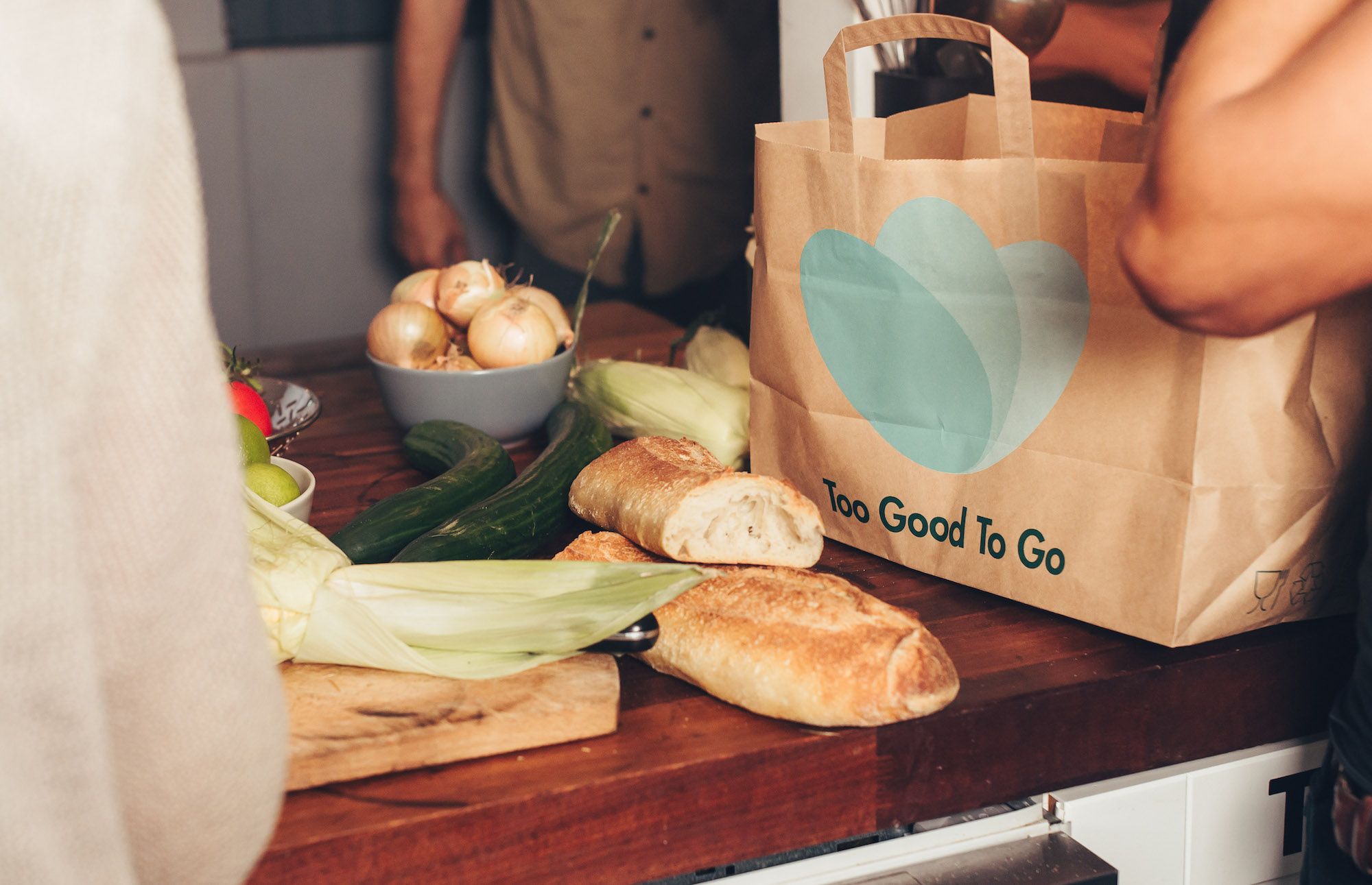 A photo of bread, onions, and zucchini on a wooden table (left) and a large brown paper bag with three blue circles and the words