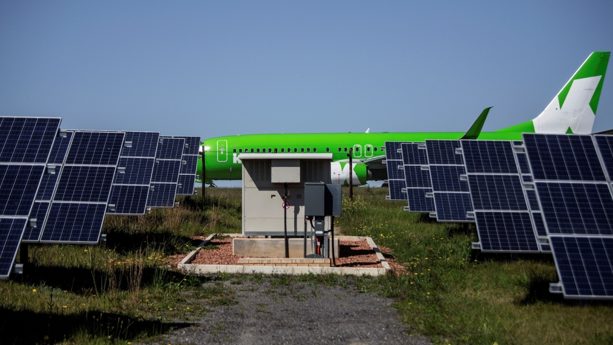 green airplane behind solar panels