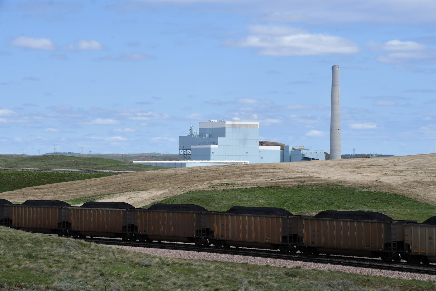 A coal plant in the distance with a train full of coal going by in the foreground