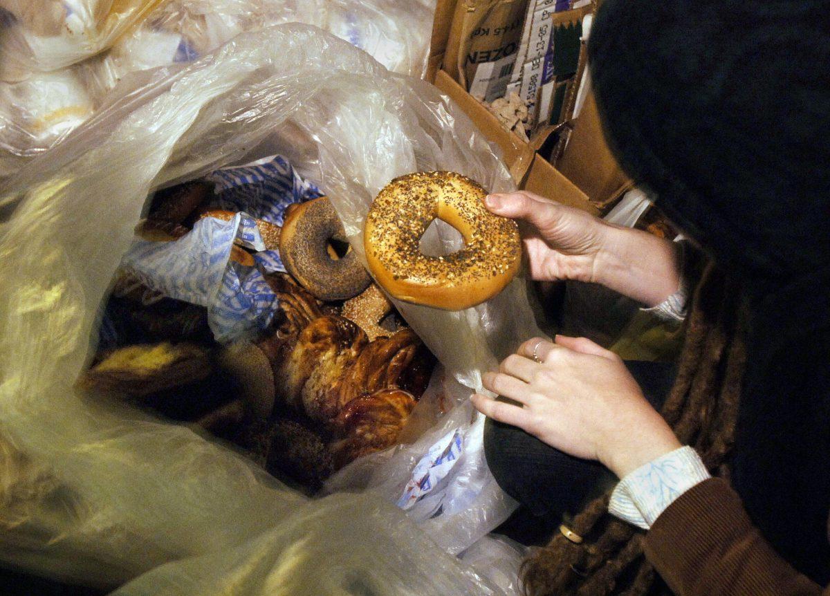 مردی دانه های نان شیرینی را روی کیسه زباله پر از کالاهای پخته شده نگه می دارد.