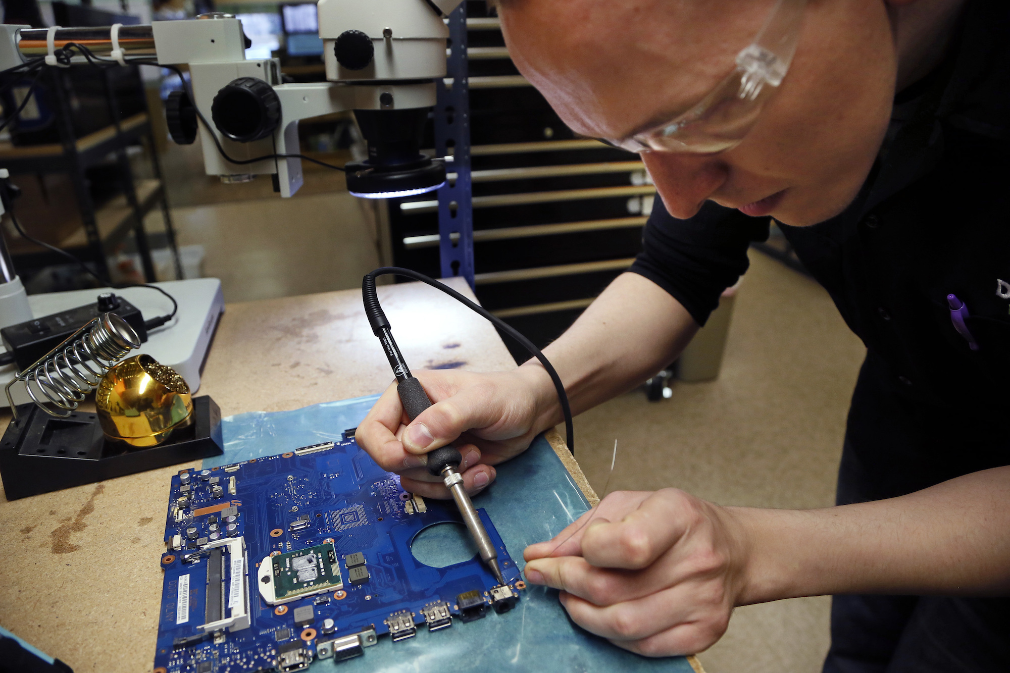 A photo of a man wearing goggles leaning over blue laptop motherboard while holding a tool