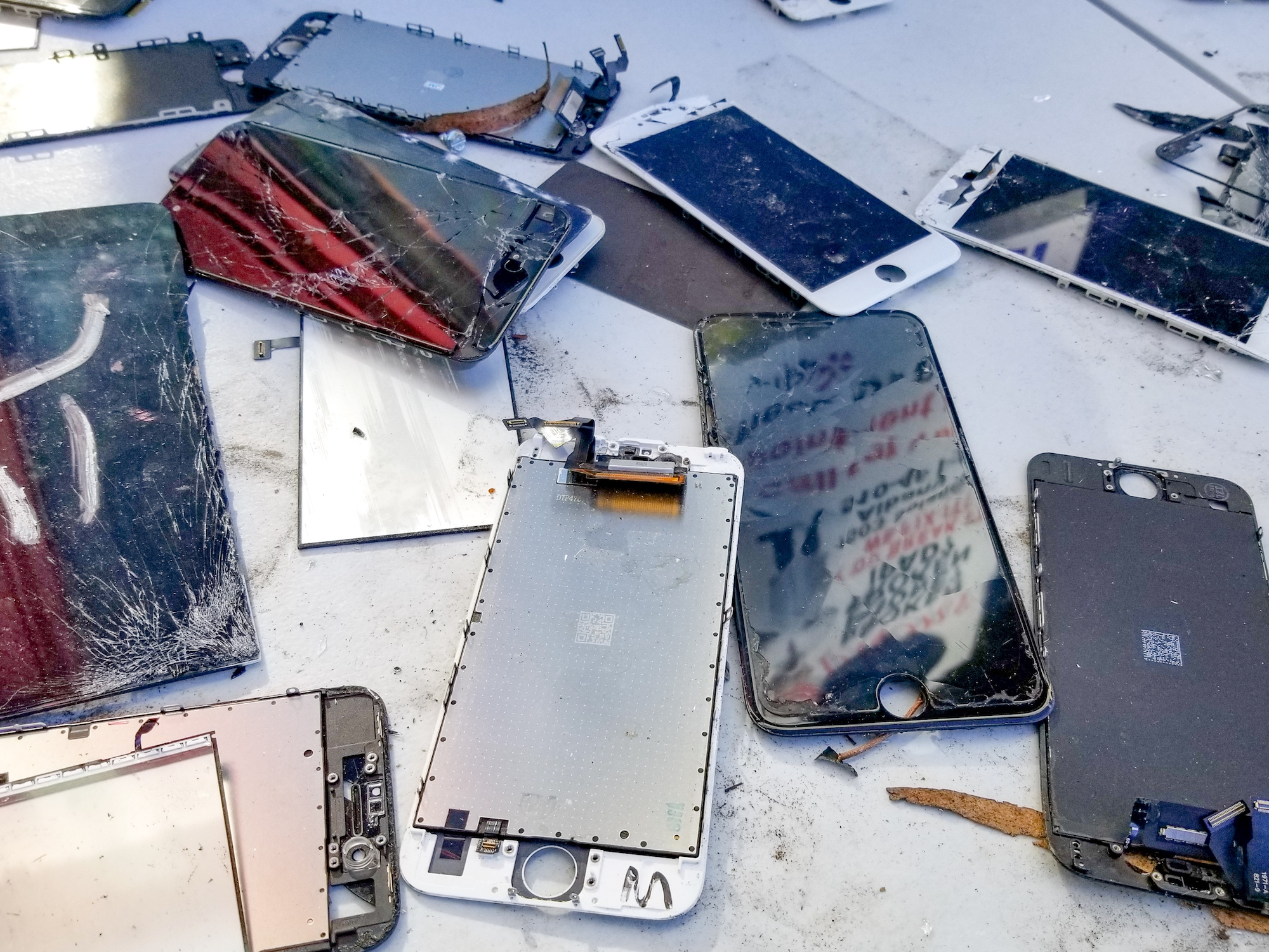 a close-up photo of broken cell phones of various types