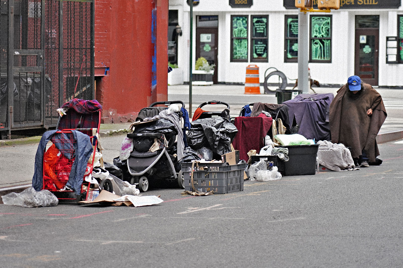 یک مرد بی خانمان با وسایلش در خیابانی در نیویورک نشسته است.