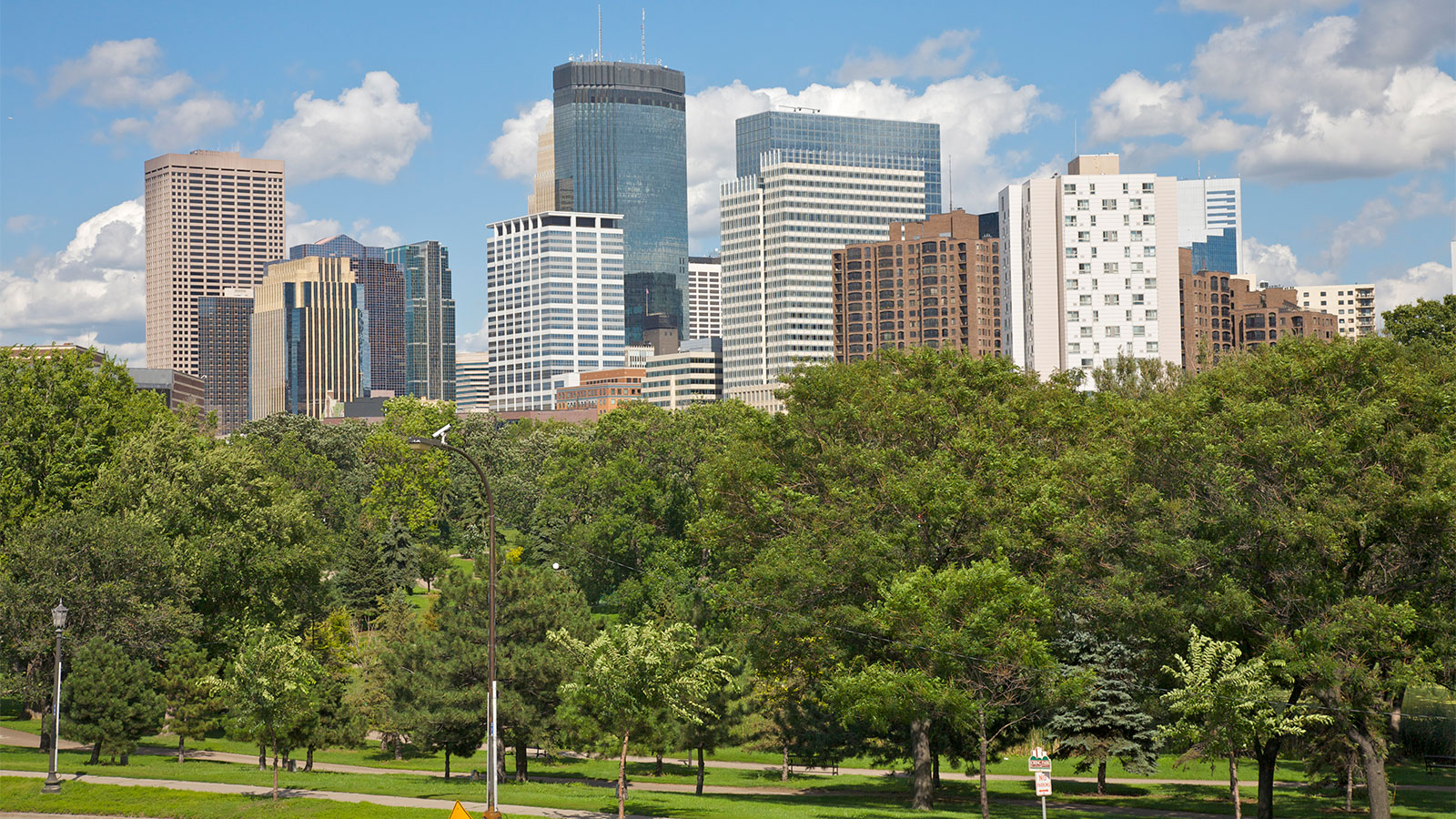 A picture of Minneapolis skyline featuring a park in front of downtown skyscrapers.