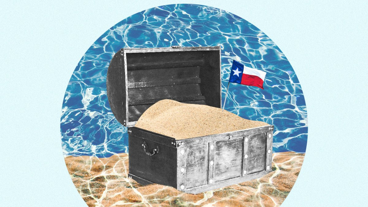 A treasure chest filled with sand and a small Texas flag