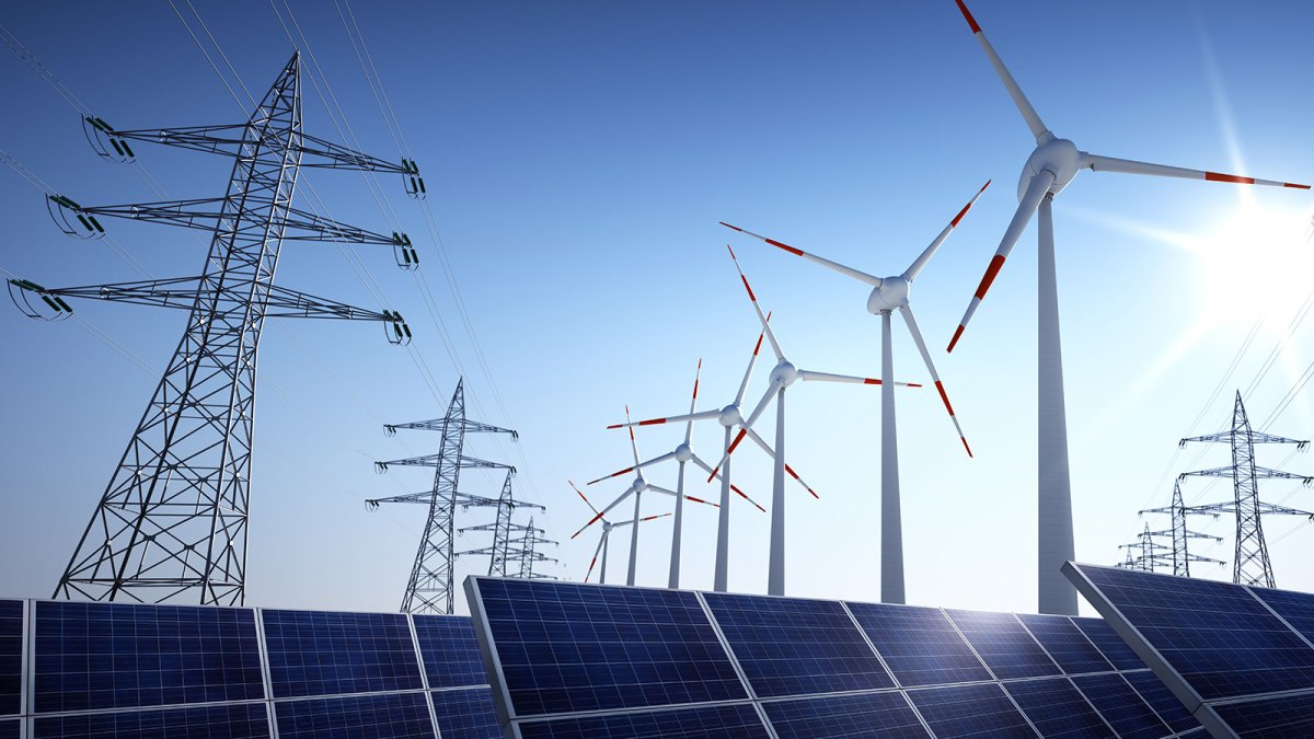 Low angle photograph of solar panels, wind turbines, and electric transmission towers