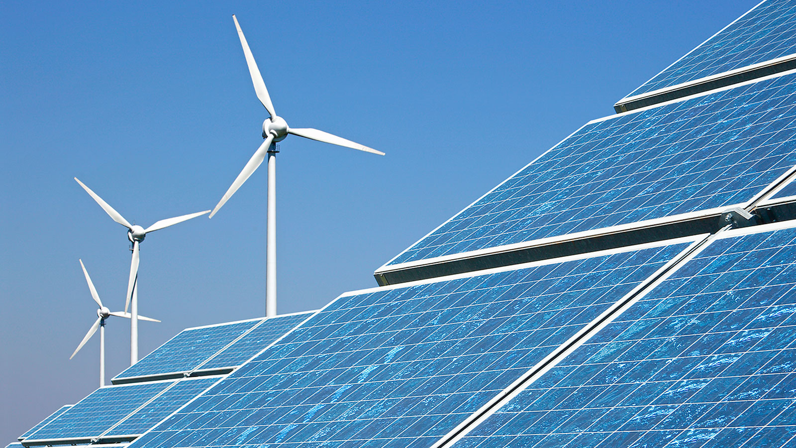 Photograph of solar panels with wind turbines in the background