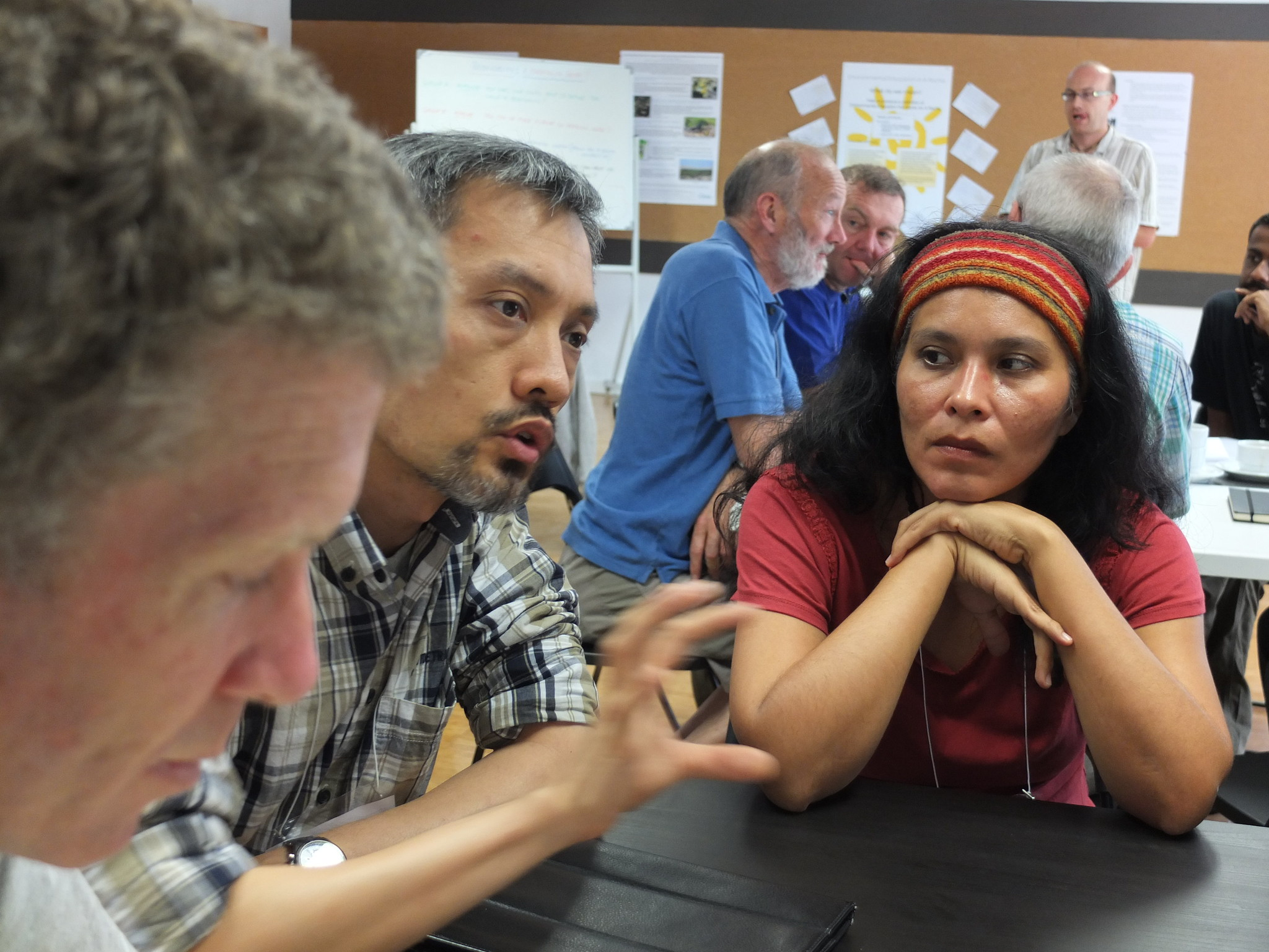 A woman in a red headband and shirt holds her hands under her chin while leaning forward on a table. She is listening to a man with graying hair and a plaid shirt as he gestures with his hand mid-sentence.