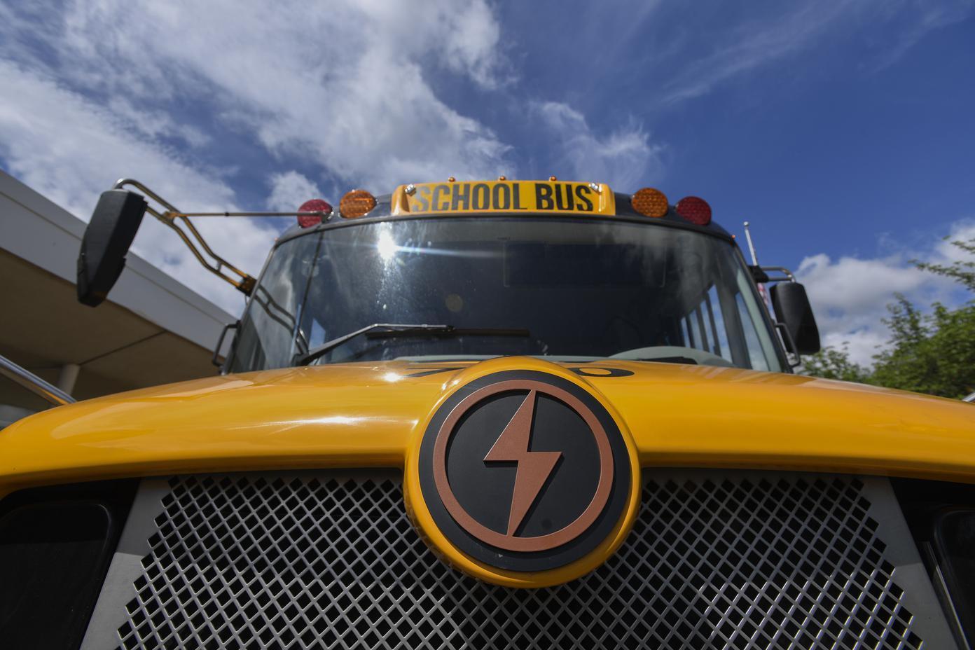 نمای نزدیک در جلوی اتوبوس زرد رنگ مدرسه با یک آرم بزرگ پررنگ در جلو