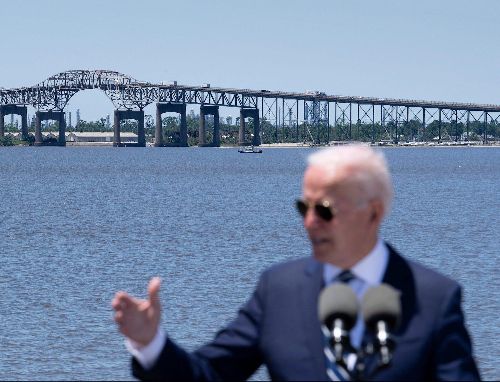 biden speaking in front of bridge and water