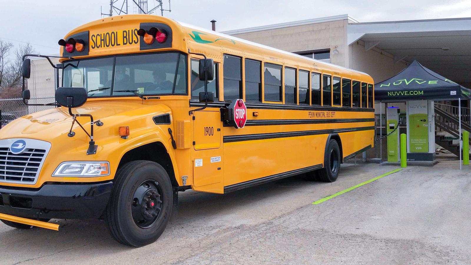 """اتوبوس مدرسه زرد در مقابل یک ایستگاه شارژ سرپوشیده کوچک در فضای باز با یک نوشته پارک شده است """"نووو"""""""