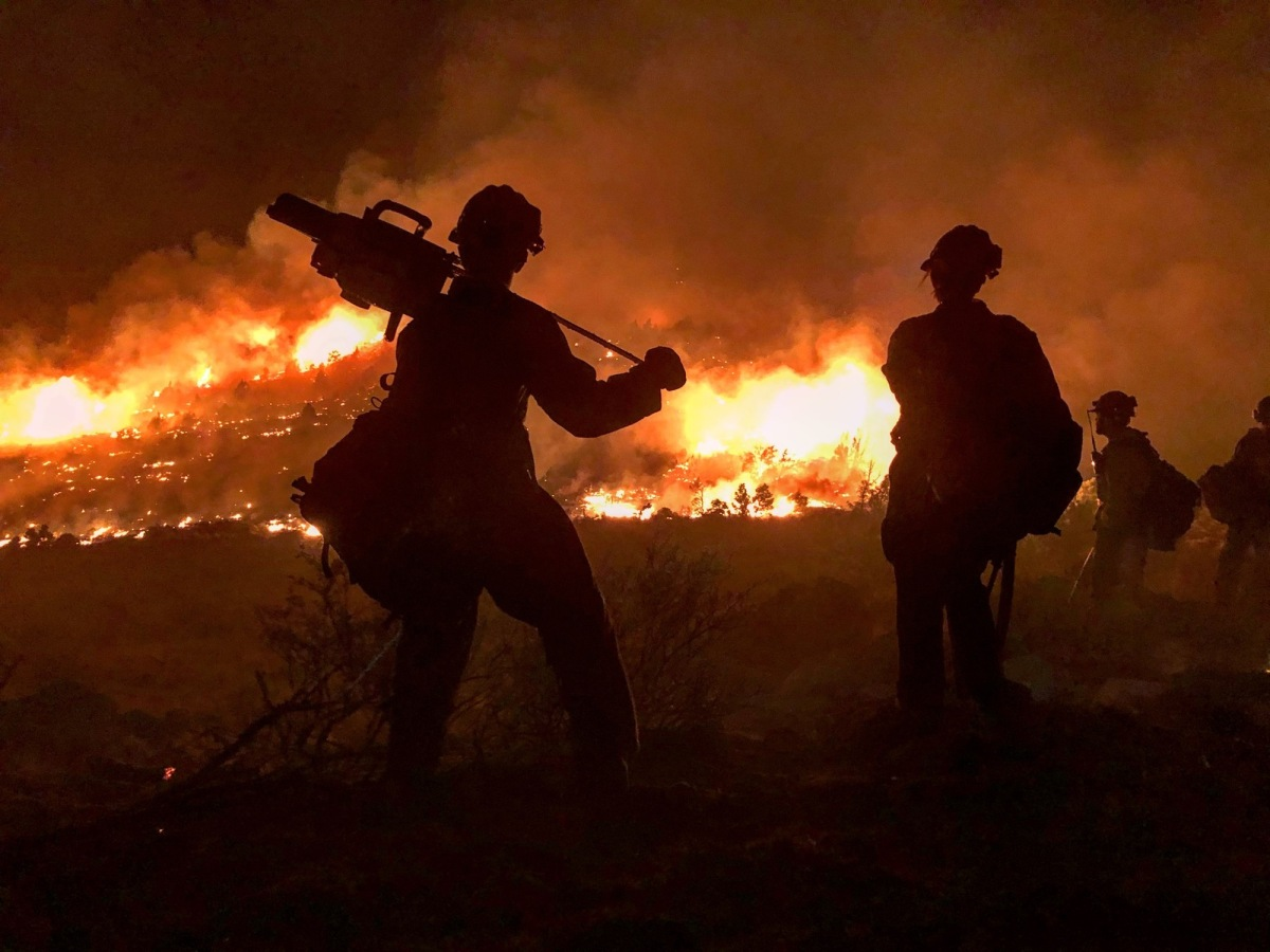 Fire blazing in the backgroud with two hot shot silhouetted in the foreground as they attempt to fight California wildfires