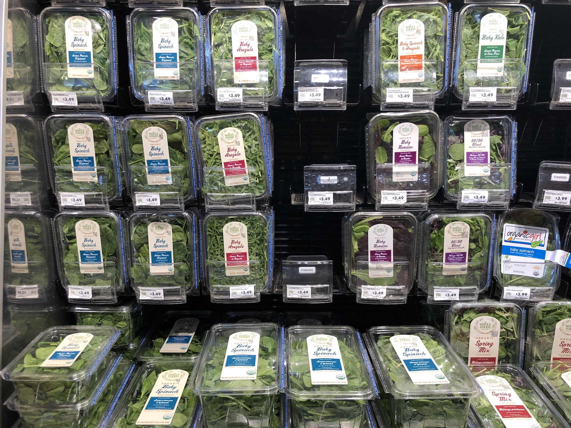 A wall of baby greens mixes each in its own plastic clamshell in a salad aisle