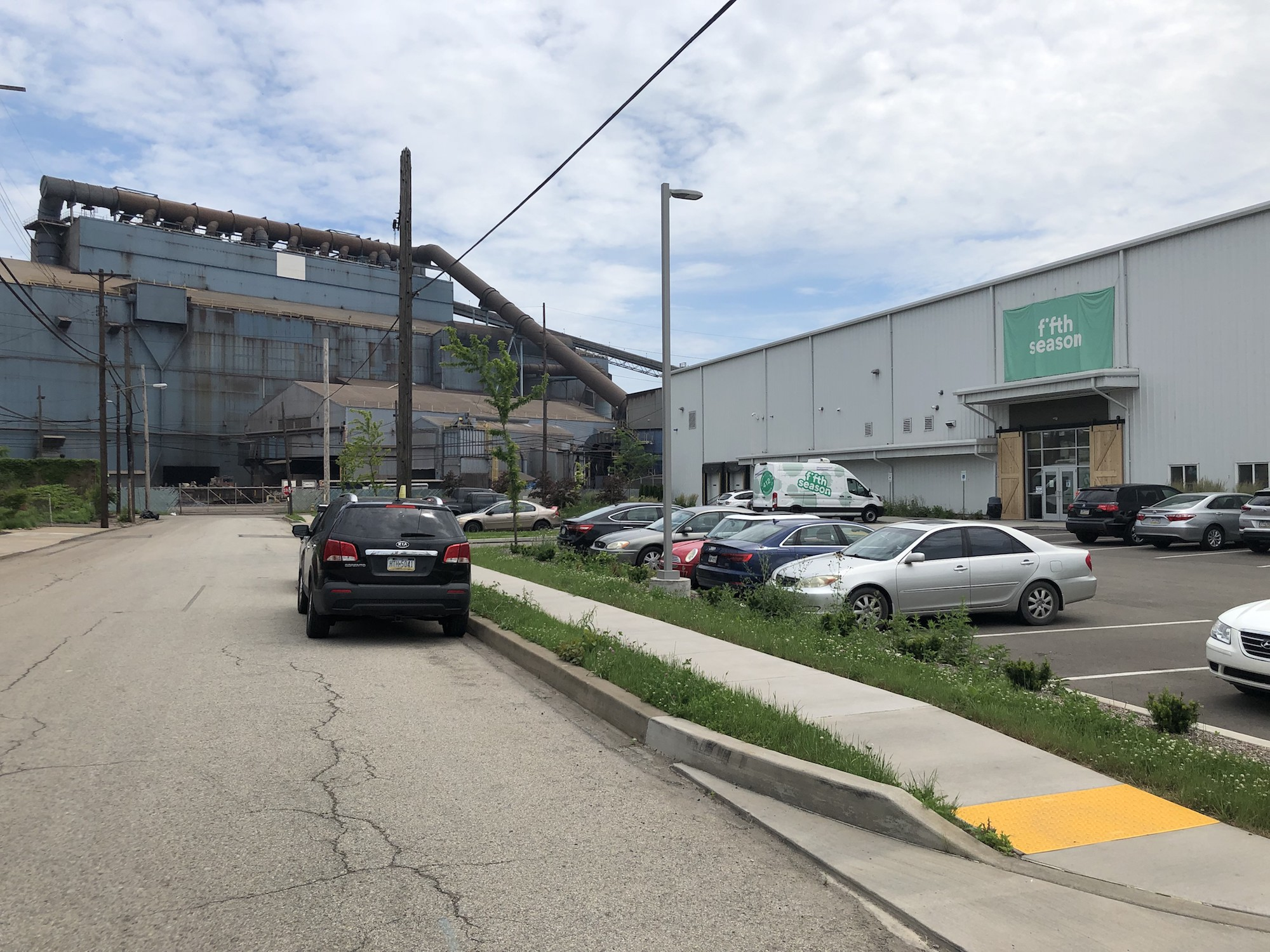 """a gray warehouse with a green sigh that says """"fifth season"""" in an industrial neighborhood"""