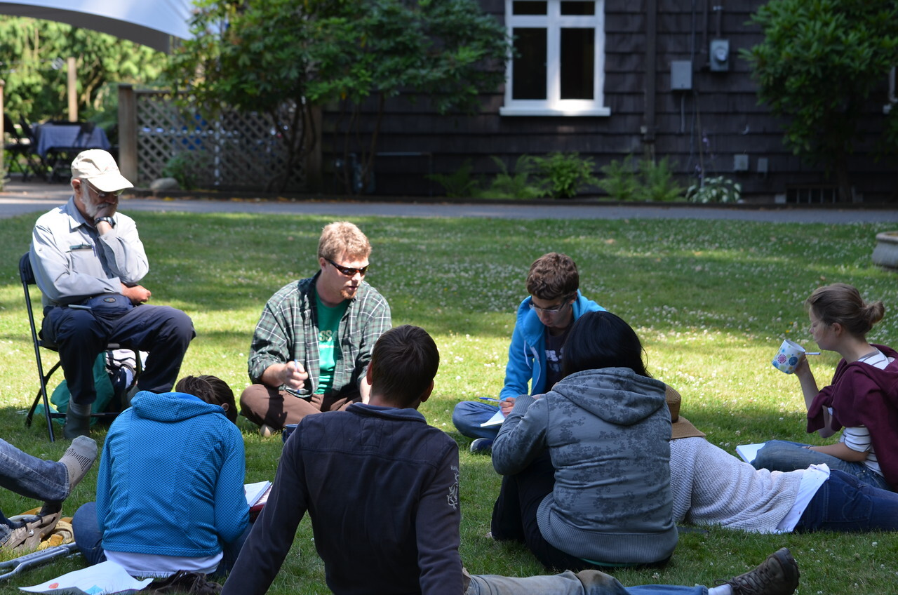 a group of people sitting in a circle in conversation on a manicured green lawn