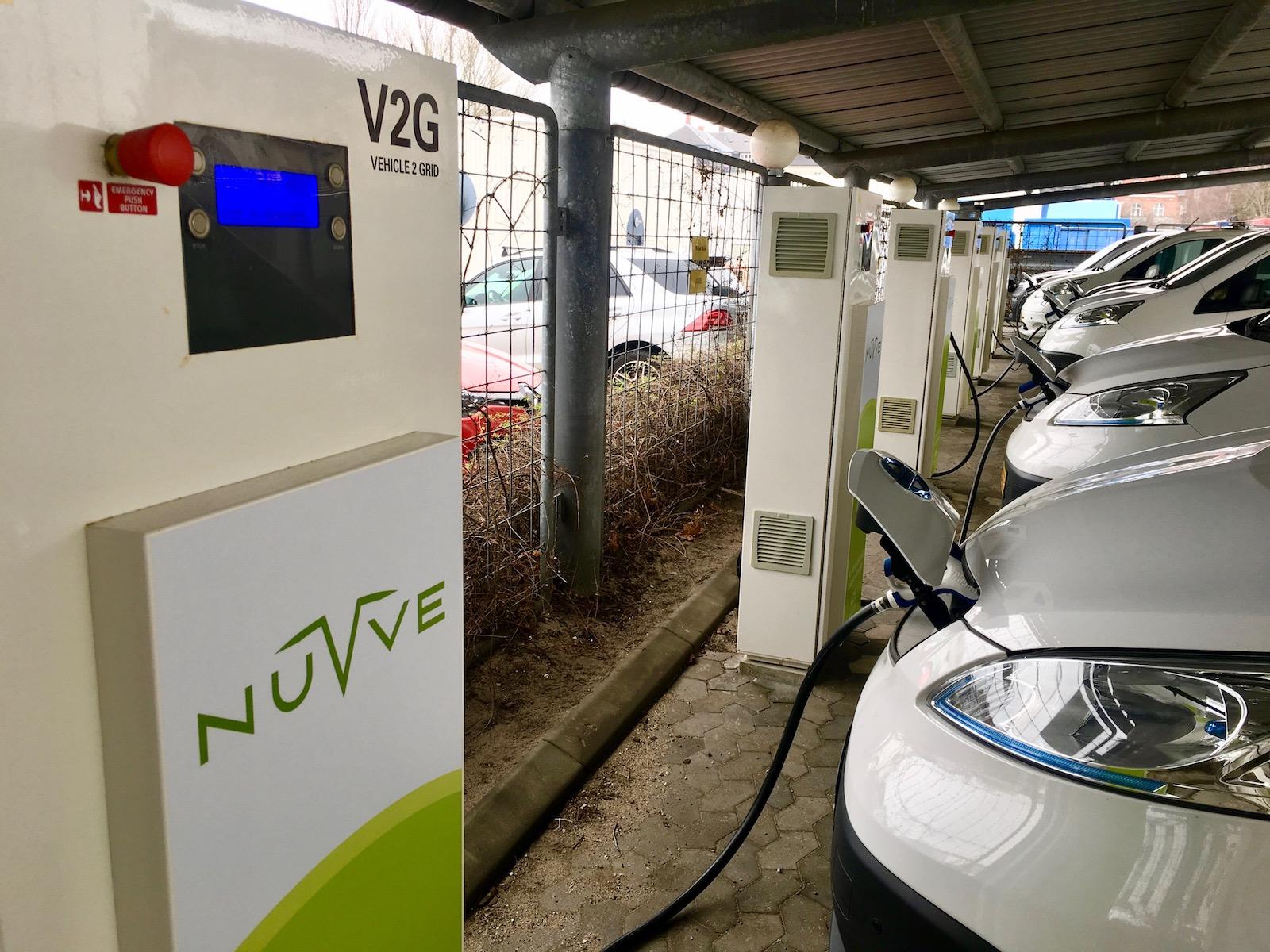 """تعدادی از اتومبیل های براق و سفید در شارژرهای دارای برچسب سبز و سفید گنجانده شده است """"Nuvve V2G"""""""
