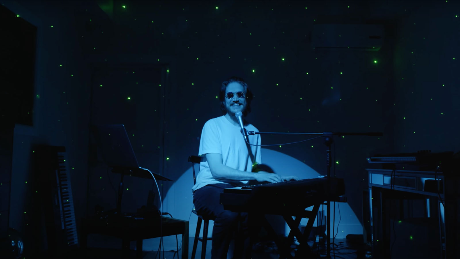 A man wearing sunglasses plays the keyboard while a blue spotlight shines on him, with a starry sky projected in the background