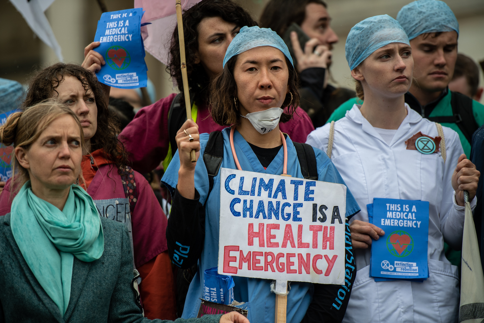 """a group of protesters, with a woman in a scrubs and a surgical mask standing in the center. She holds a sign that reads, """"climate change is a health emergency"""""""