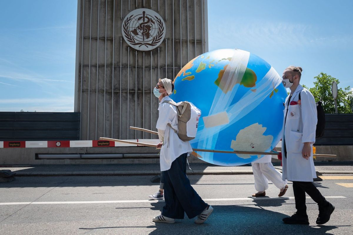 two people in white medical coats carry a blow up globe covered in bandages as they walk in front of a building with a medical logo
