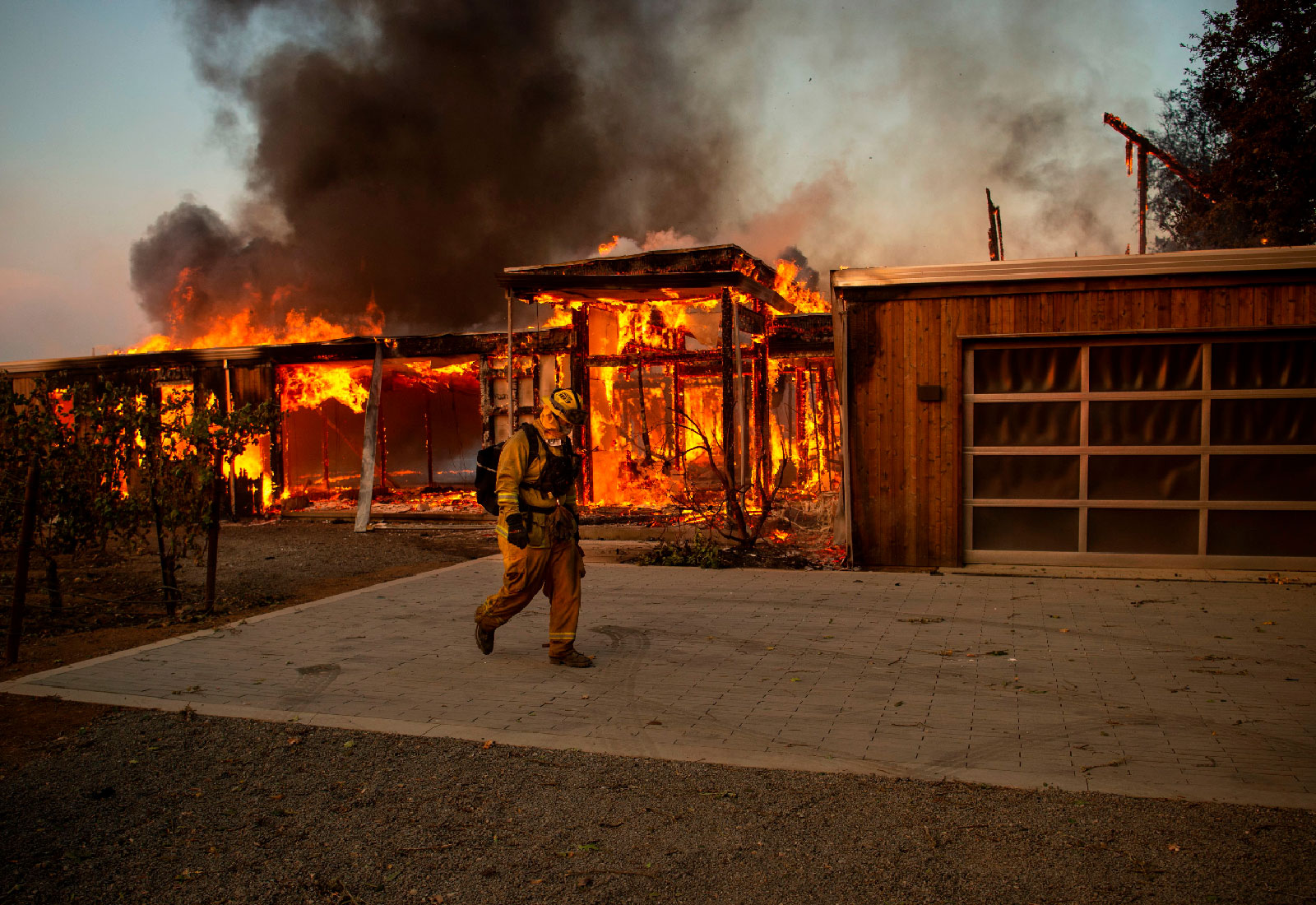 A firefighter walks past a burning house