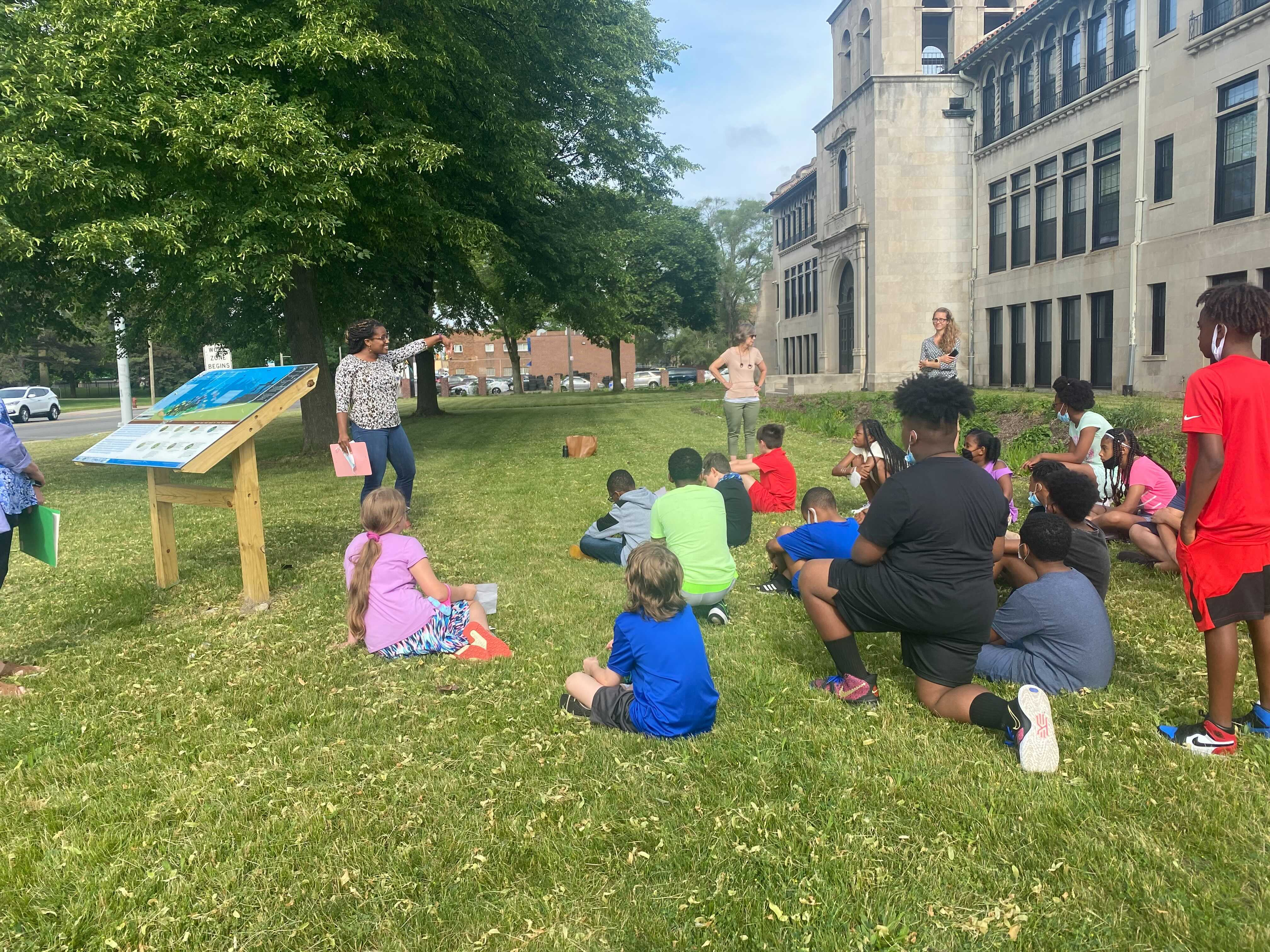 Kids sit on the grass in front of a representative from the National Wildlife Federation as she congratulates them for their work and presents them with a certificate.