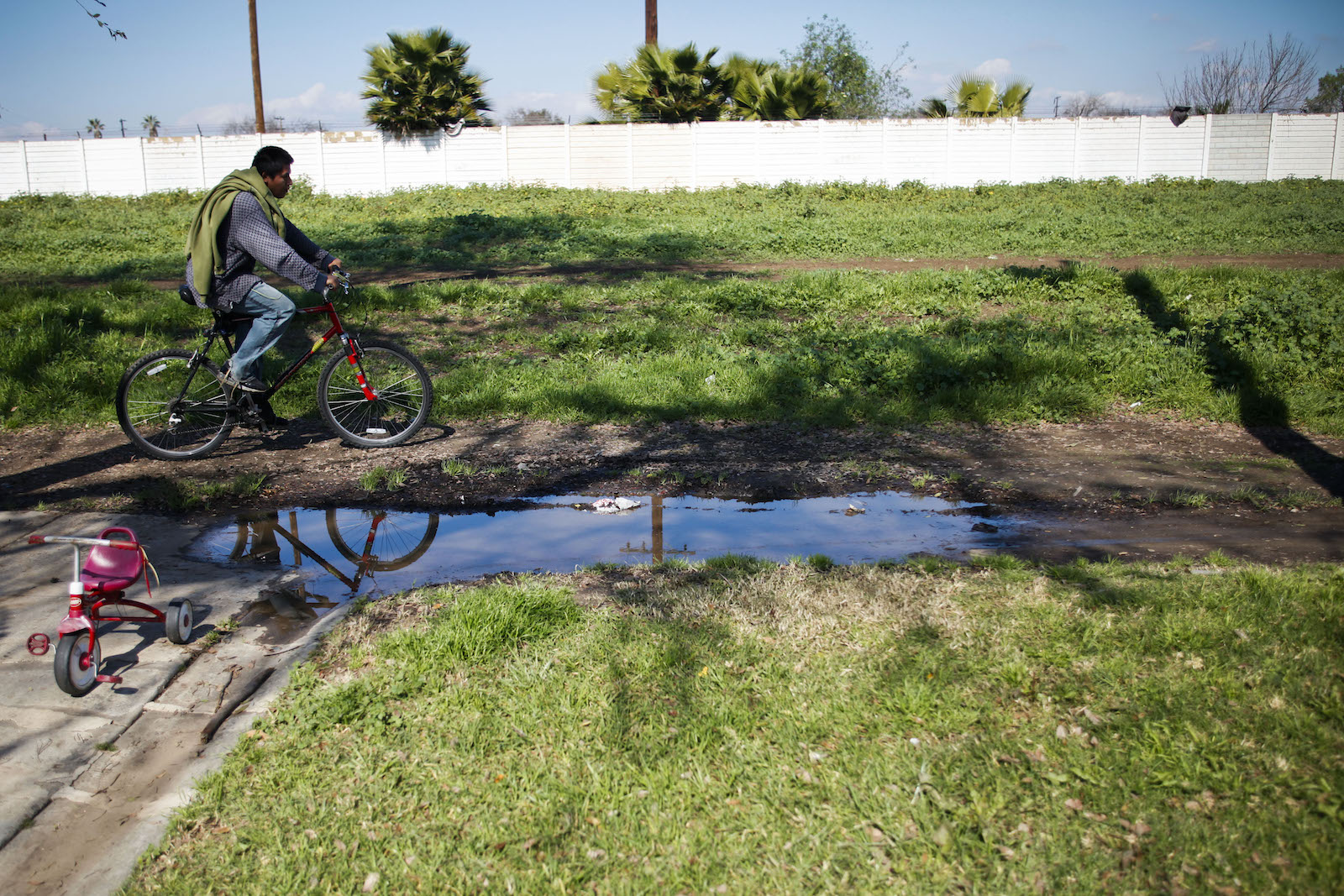 a man on a red bike pedals near a muddy pool of water in a green field