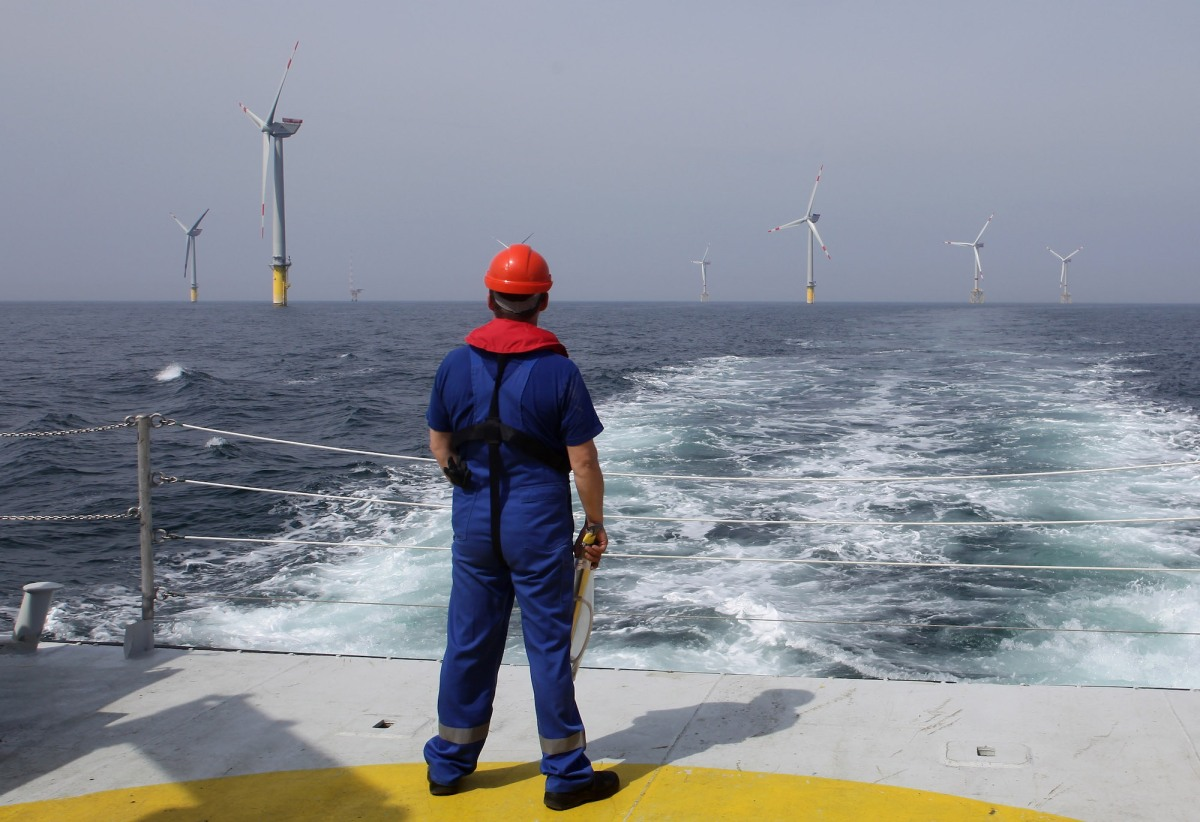 a worker in a dark blue jumpsuit and red hard hat stands on a platform looking out at several offshore wind turbines