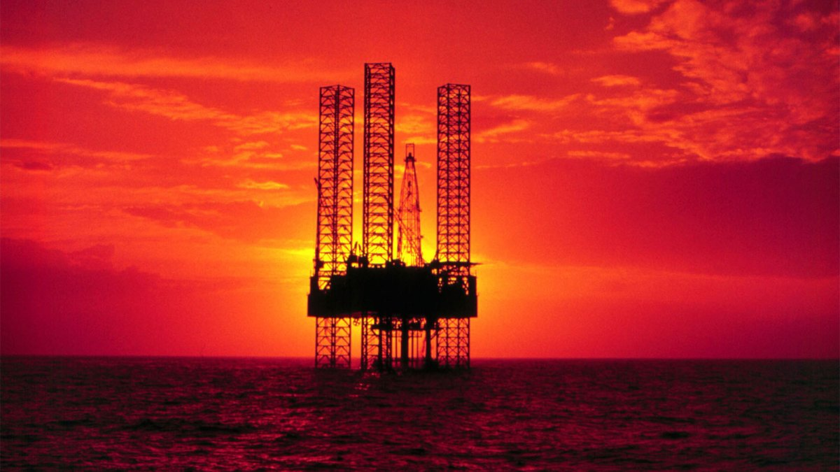 An offshore oil rig against a brilliant sunset