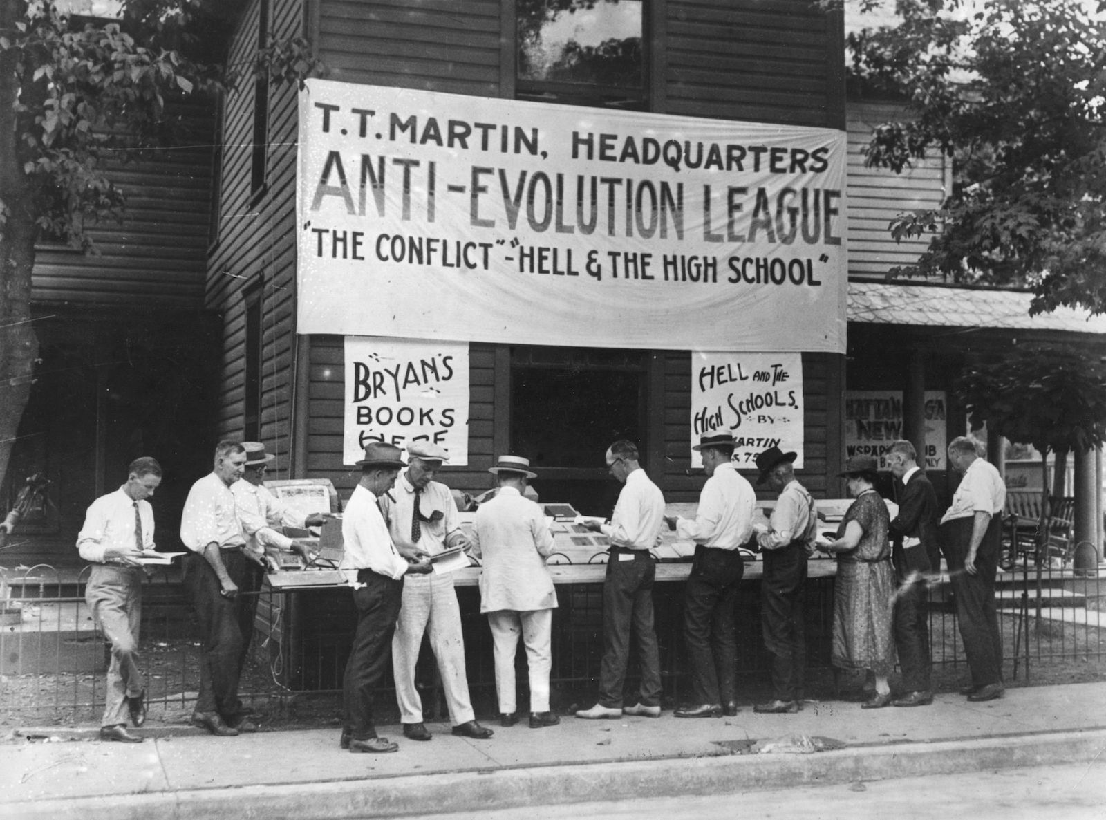 """a large sign for the """"anti-evolution league"""" hangs above a black and white scene of people in front of a book stand"""