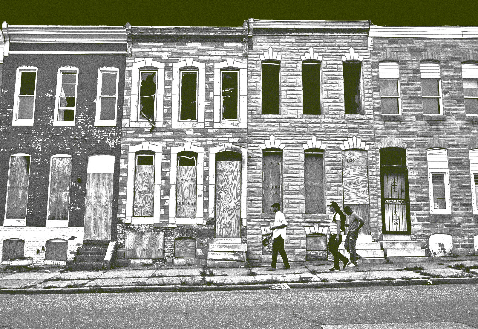 Three pedestrians pass by a row of boarded up houses in east Baltimore, Maryland.
