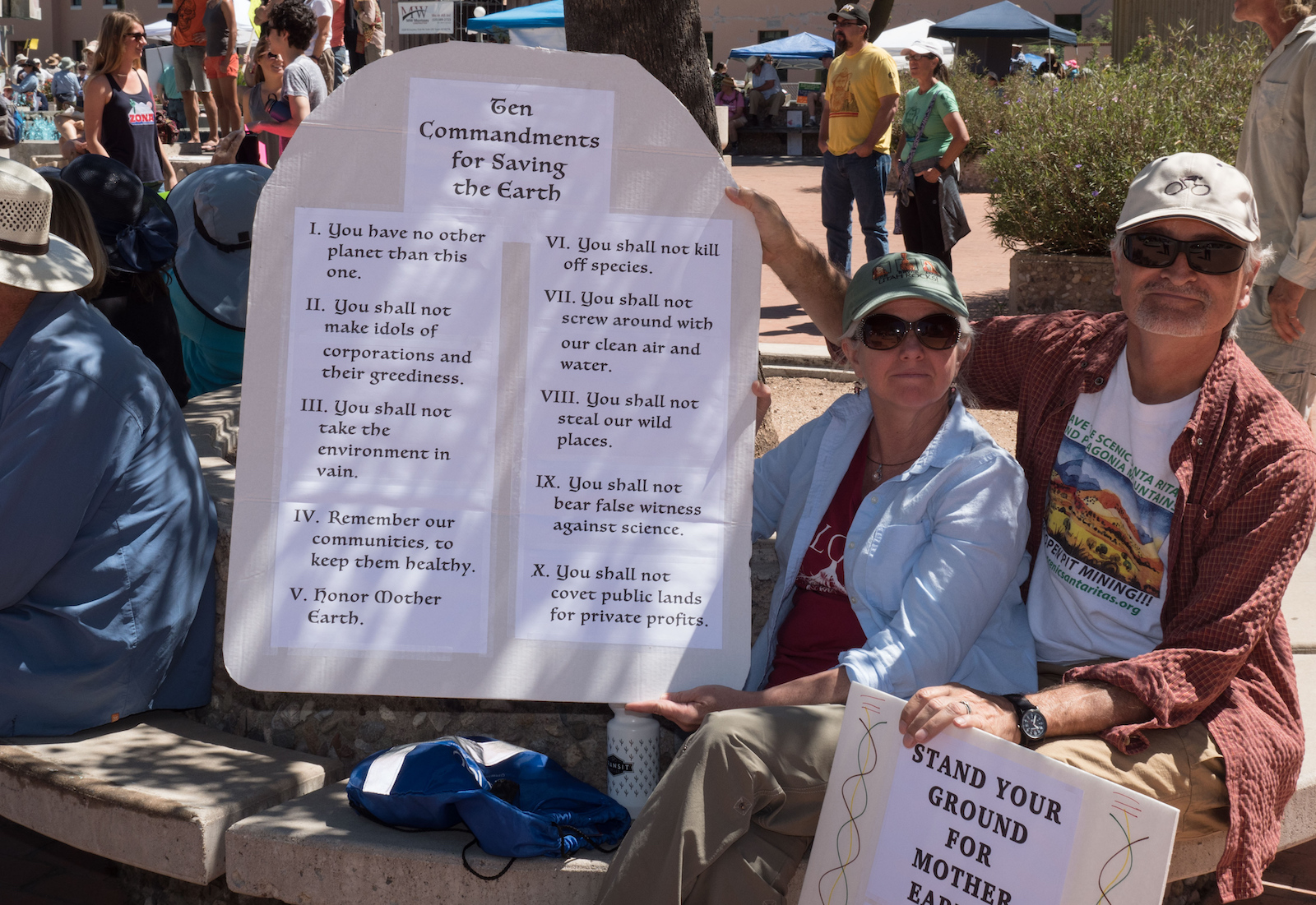 """A couple holds up a poster with the """"Ten Commandments for Saving the Earth"""" at the Arizona People's Climate March in 2017."""