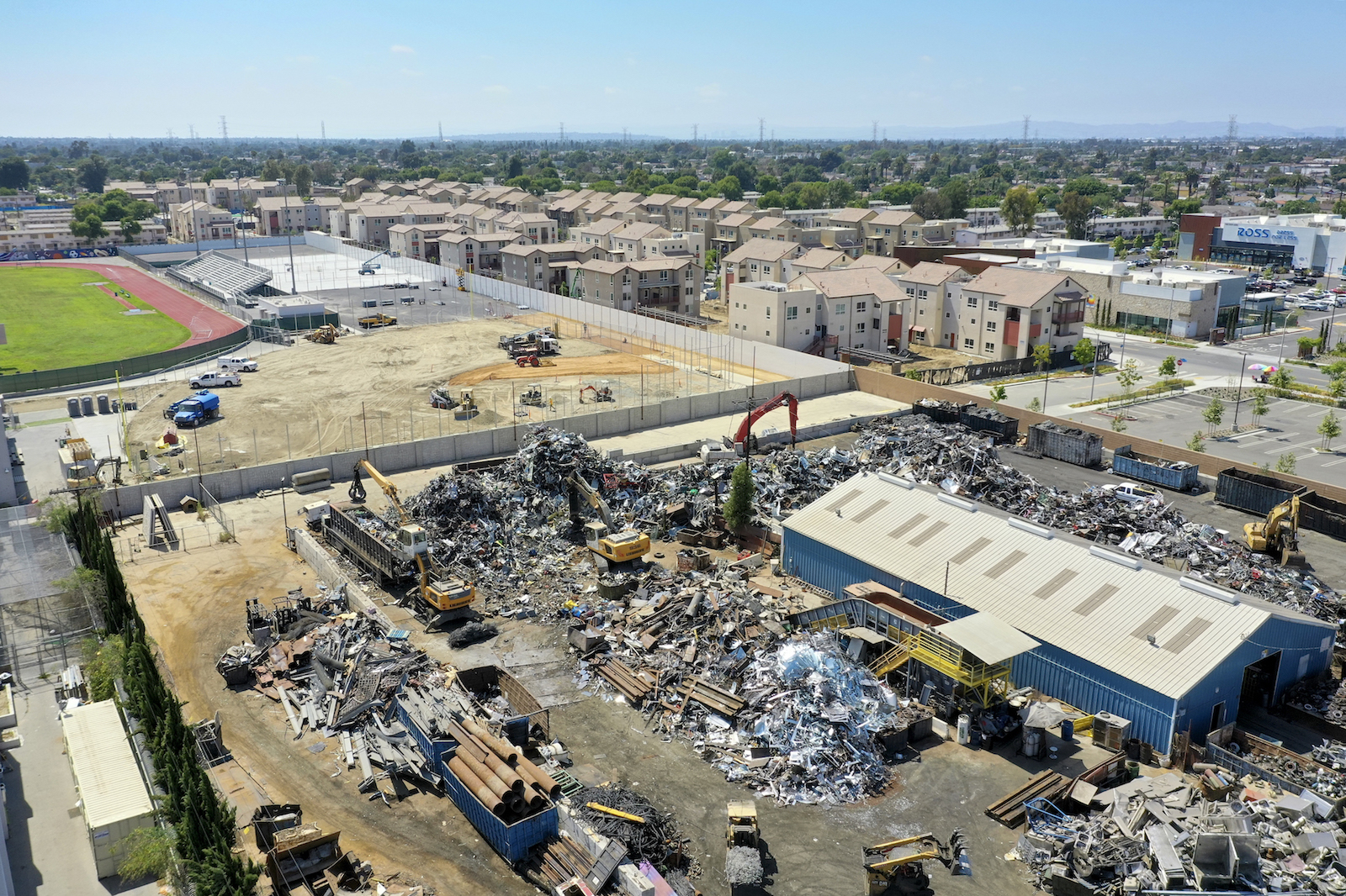 an aerial view of a large scrapyard piled high with metal pieces next to a sunny road and green sports field