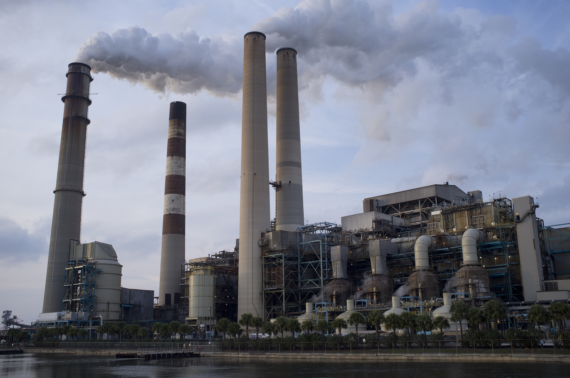 a large power plant with stacks spewing smoke