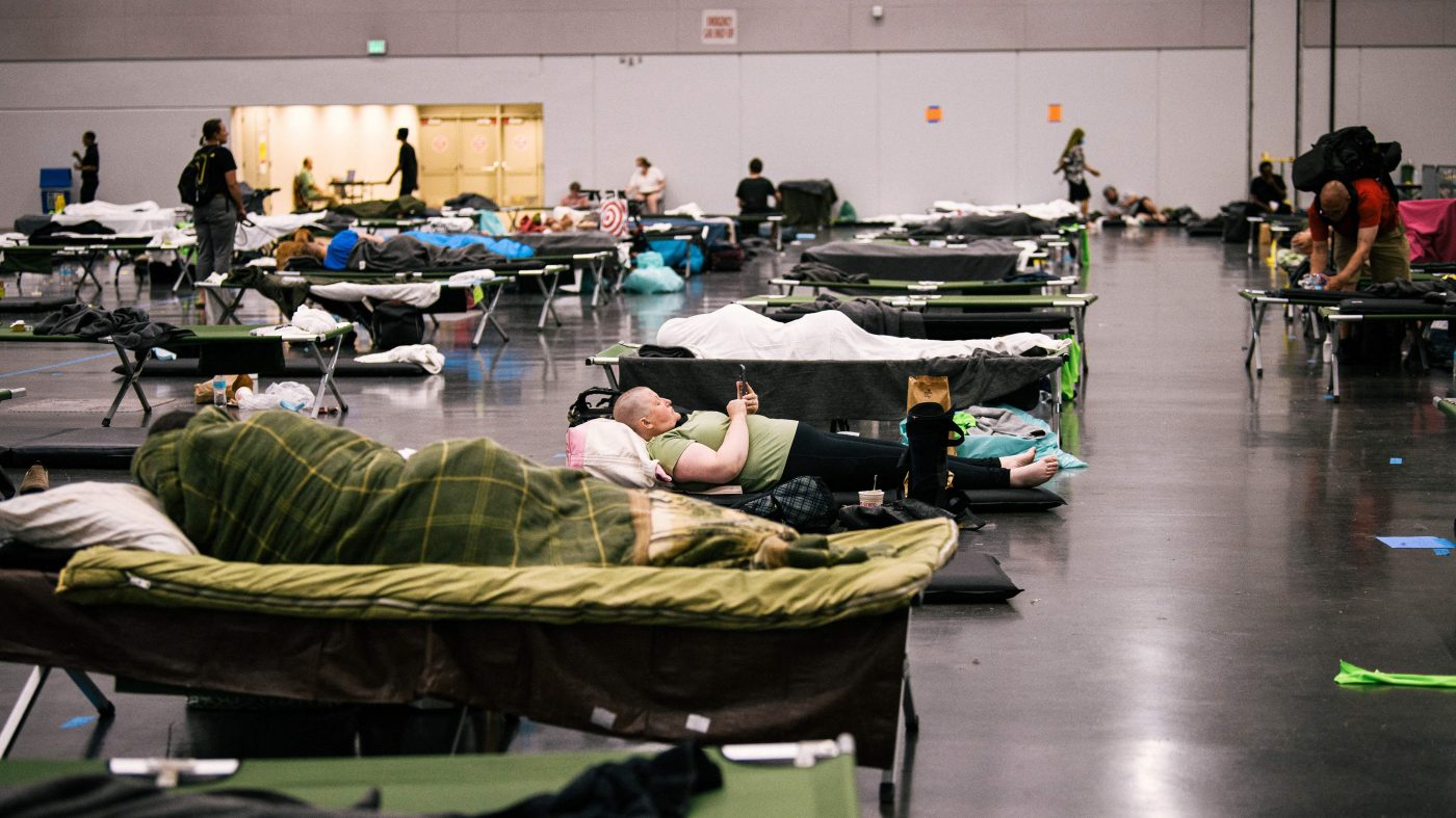 People rest on cots with blankets in a large room.