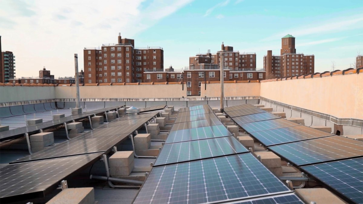Solar panels on a roof with buildings in the background