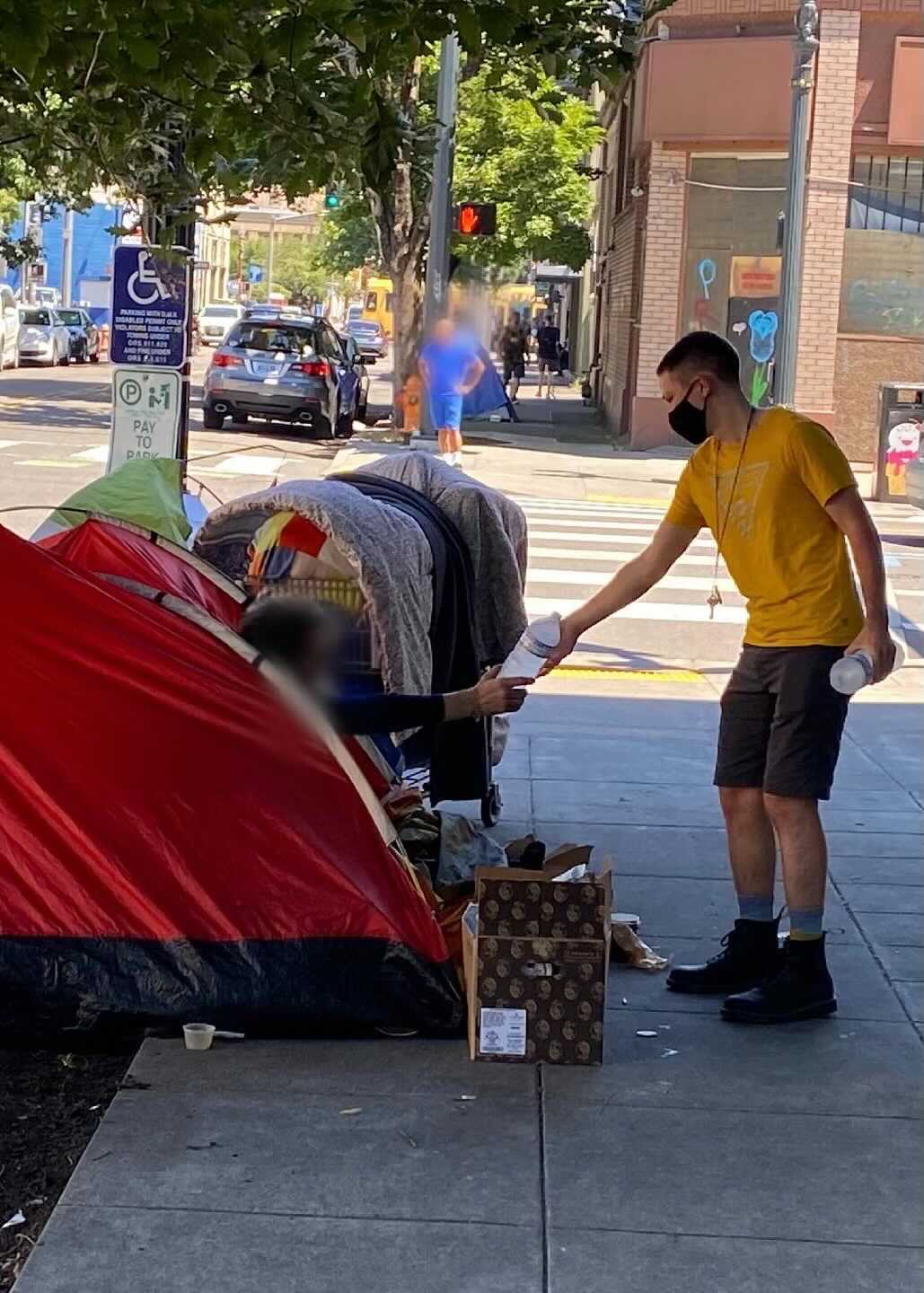 a person in a yellow shirt hands a bottle of frosty water to a person in a red tent on the streets of portland