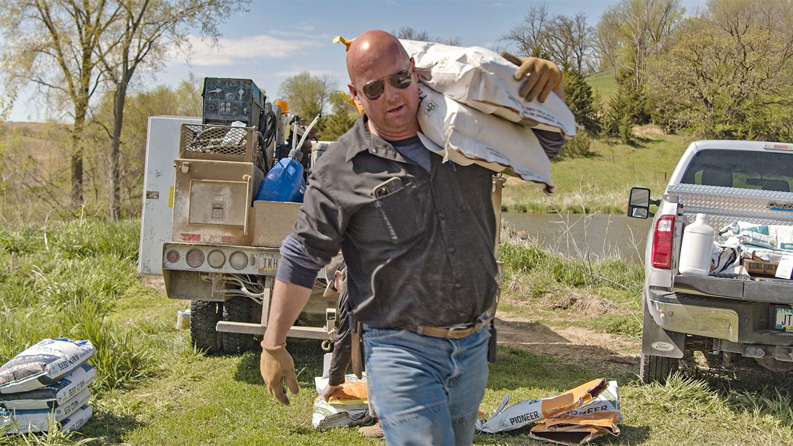 a man on a farm carries a large white sack over his shoulder