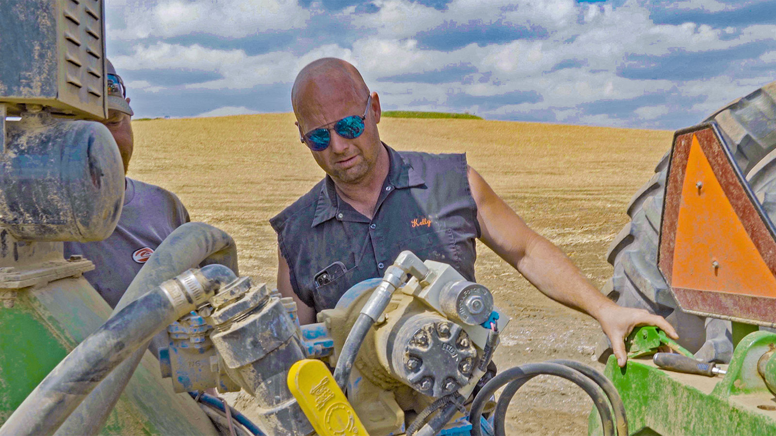 A bald man in sunglasses and a cut-off shirt looks over a piece of farm equipment