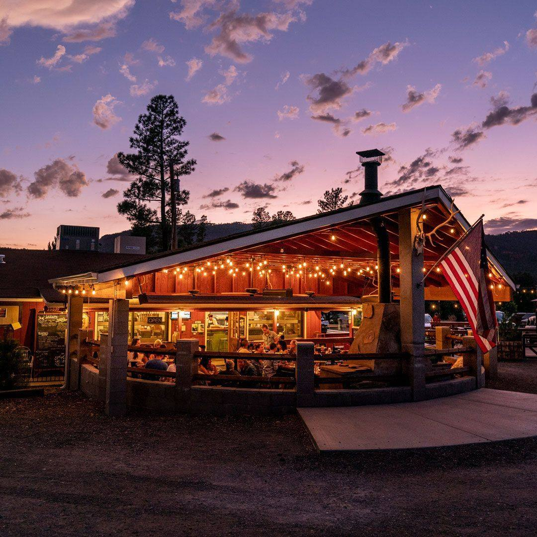 نمای بیرونی رستوران-مسافرخانه با سقفی چوبی و درختانی در پس زمینه