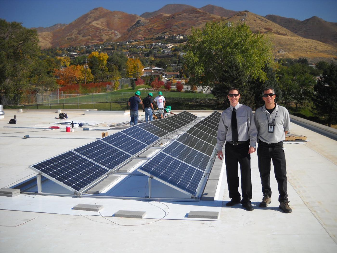 Two men standing near solar panels