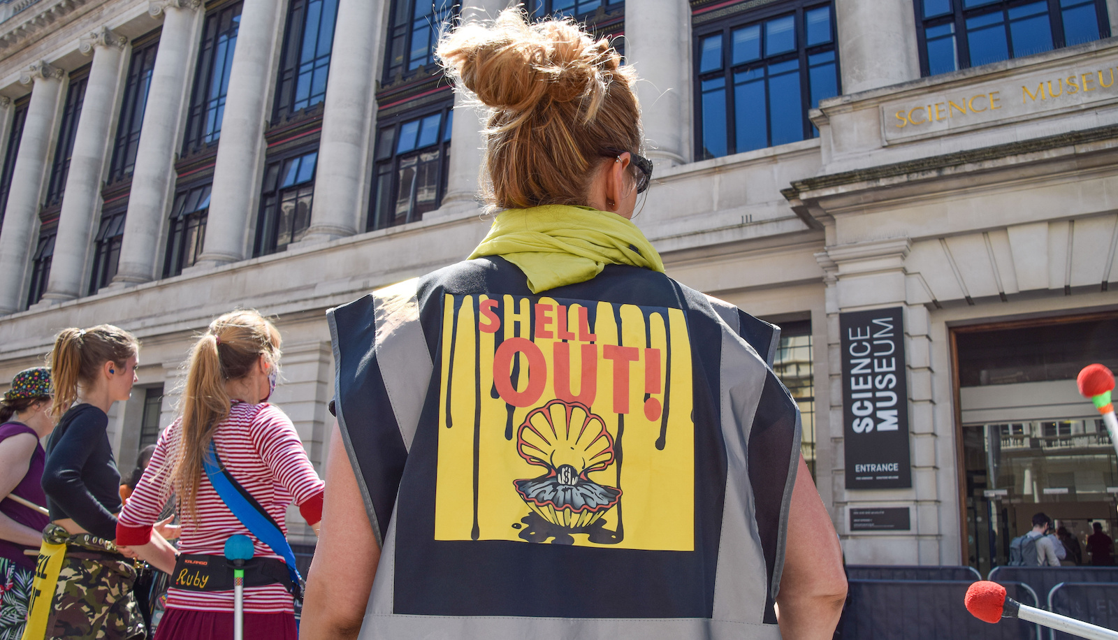 Woman stands outside UK science museum with shirt that says SHELL OUT
