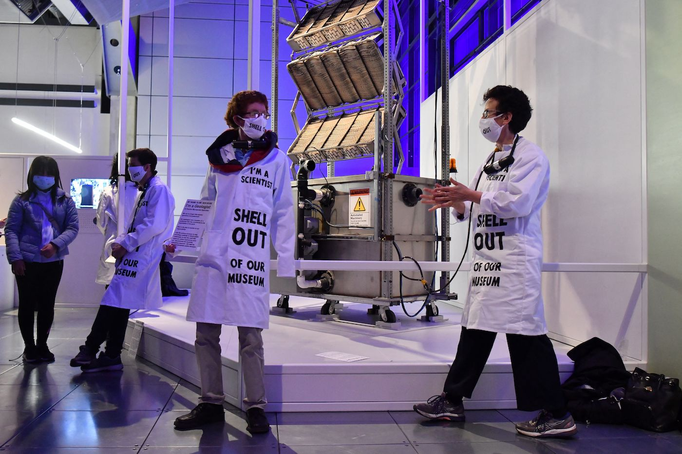 Protestors chain themselves to a museum exhibit with coats that say I am a scientist, Shell out