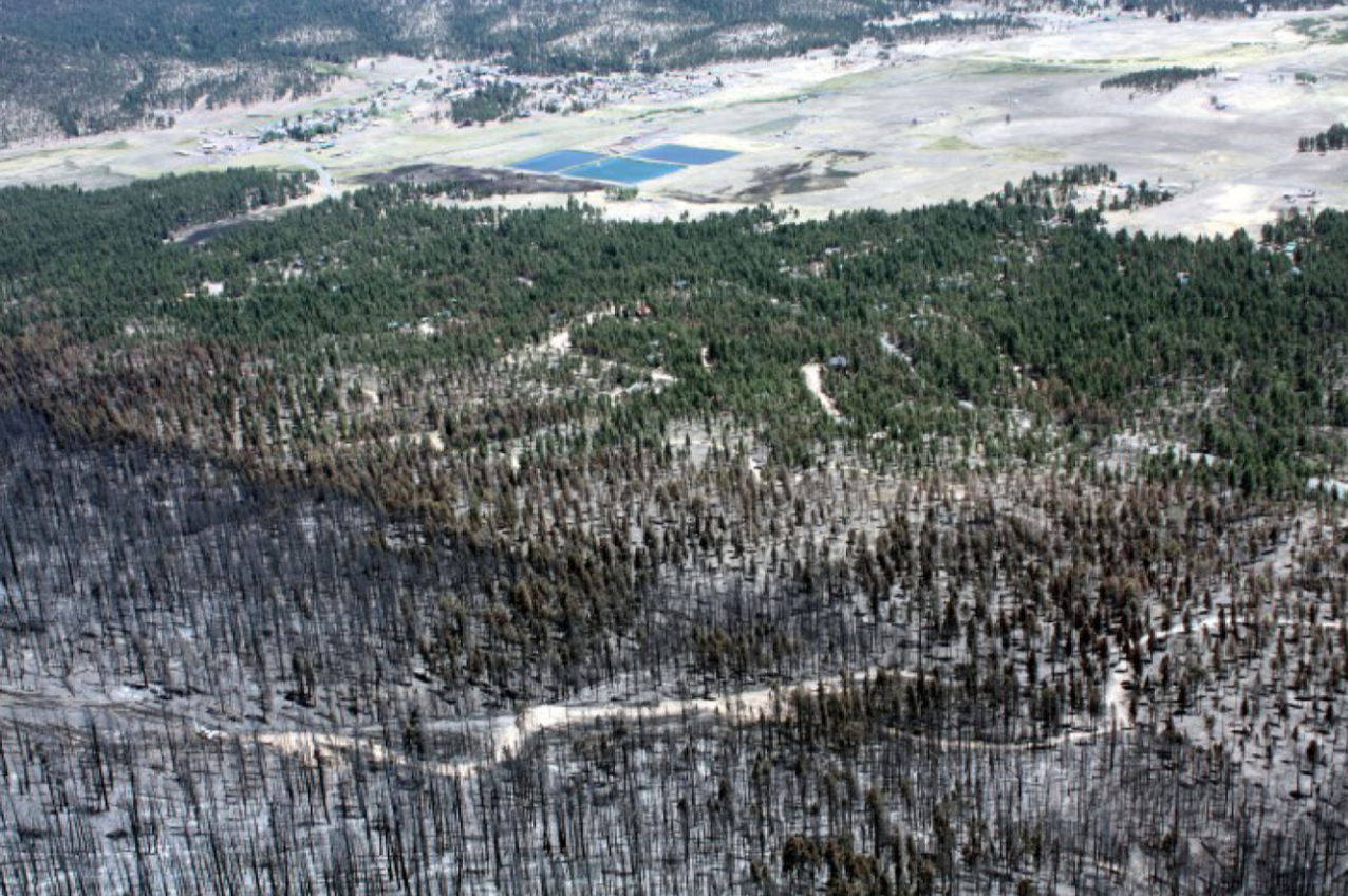 The fire burned down the hill leaving a black area, as it encountered the treatment unit (brown area) and approached residences (green area). The treatment edge is obvious as is the change in fire behavior.