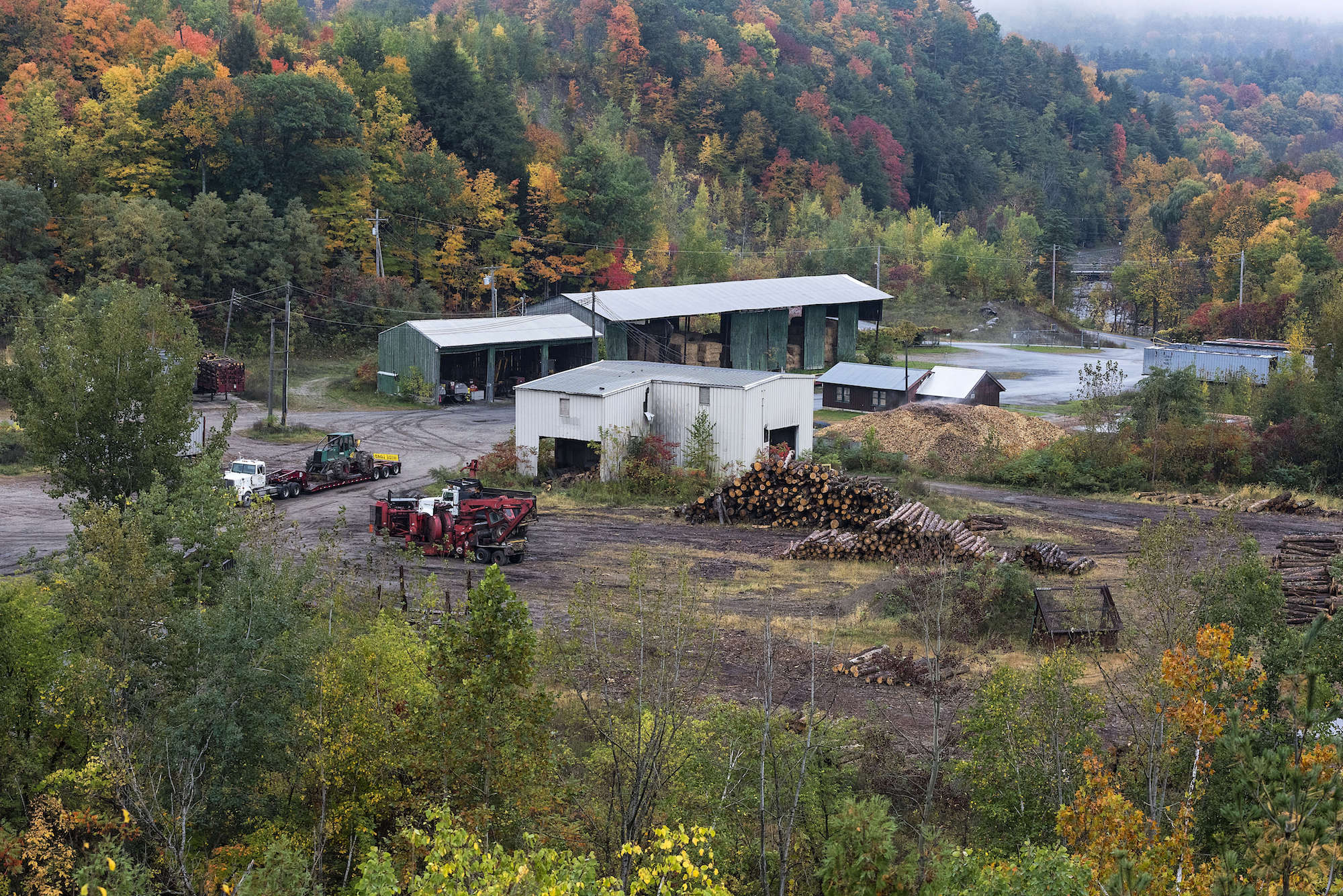 a white building with red logging equipment in the middle of fall foliage forest