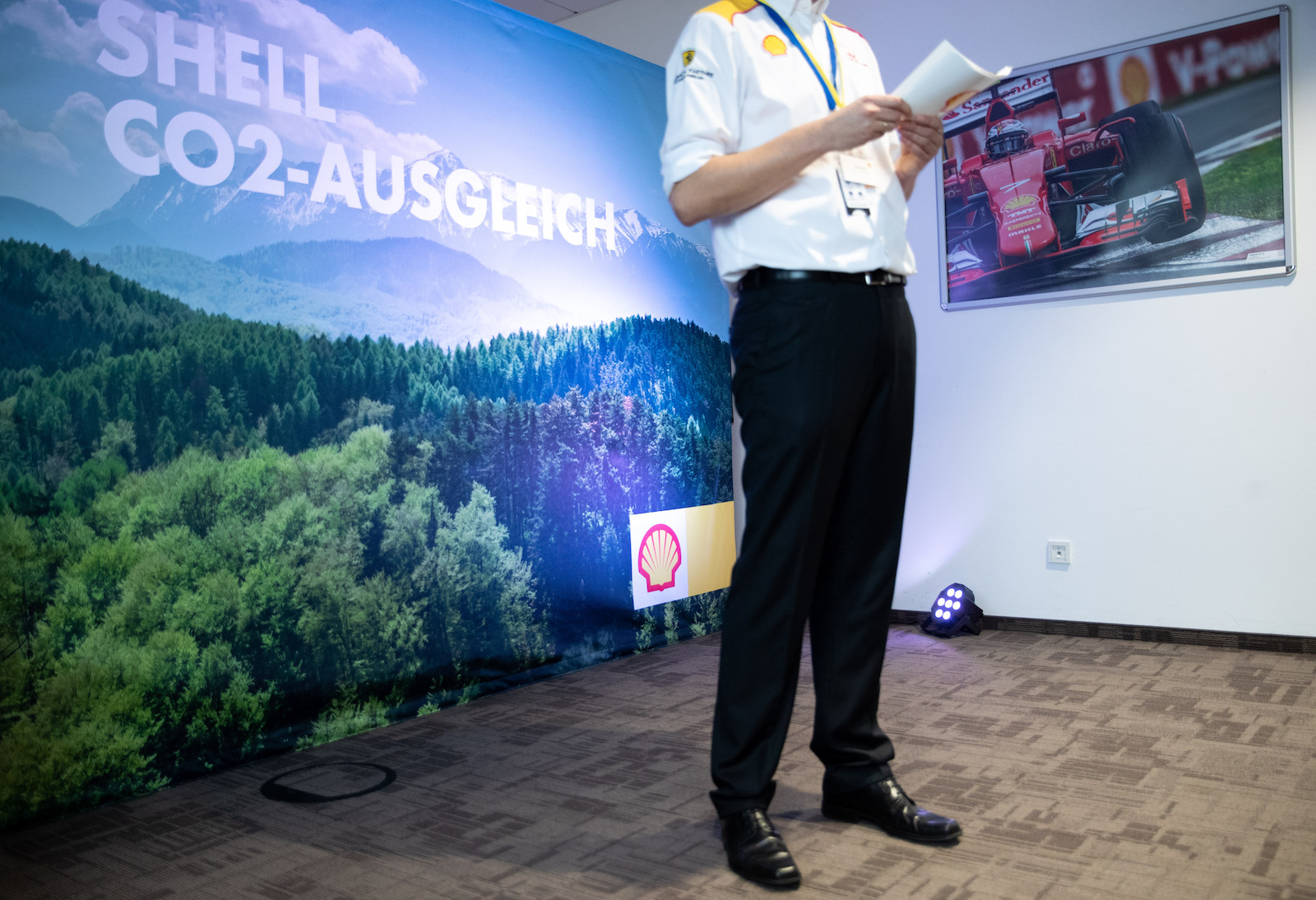 a man in a white shirt and black pans stands in front of a large mural covered in trees promoting a tree-related CO2 offset by Shell company