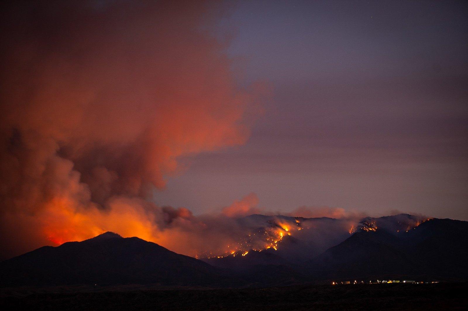 آتش سوزی در جنگل با دود بیش از یک تپه تاریک در برابر غروب خورشید نگاه می کند