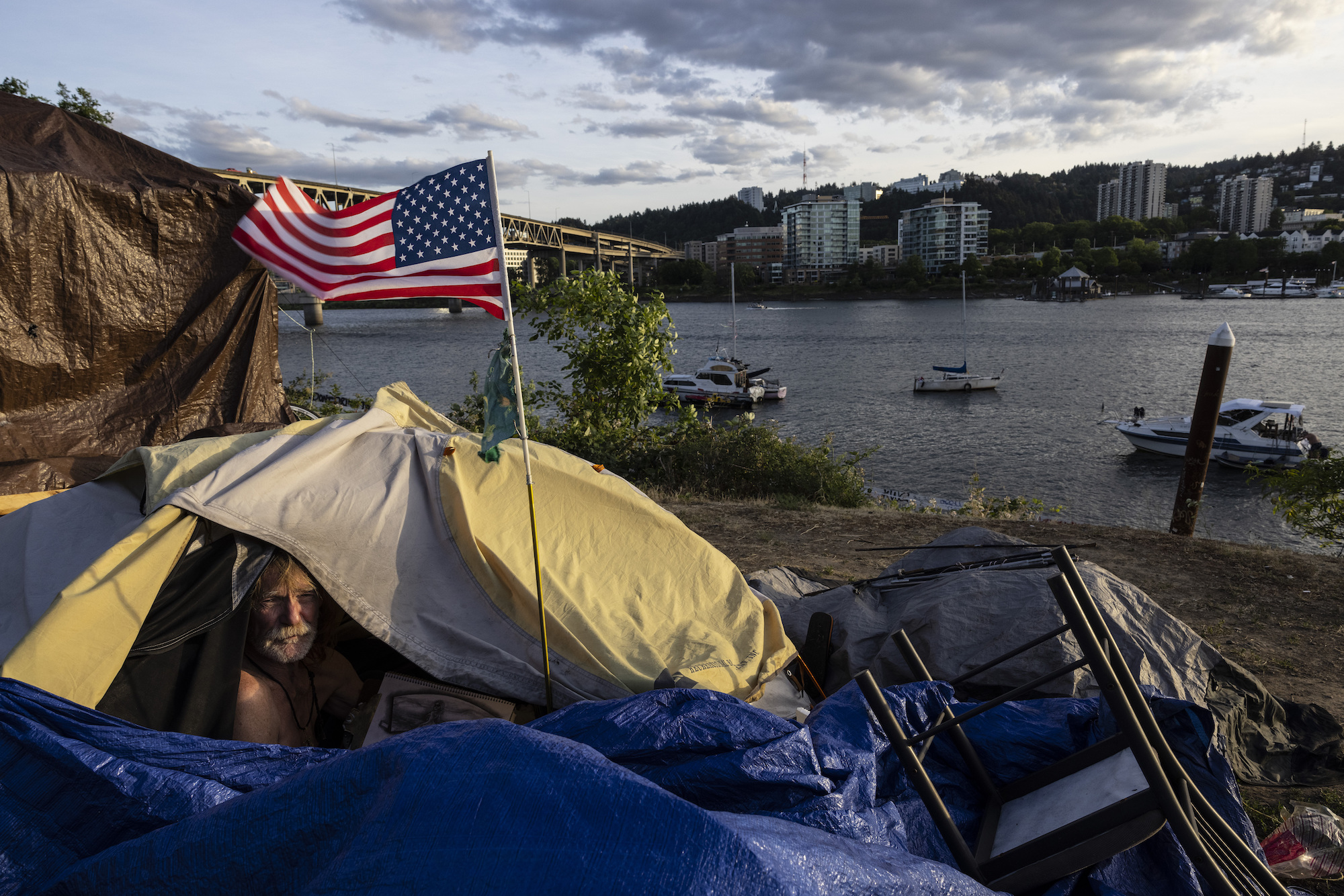 a bearded man in a yellow tent with blue tarp looks out of the flap. Outside of the tent is an American flag. The tent is on a beach with houses in the background and boats in the water.
